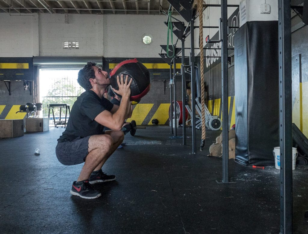 Man squatting down about to throw a wall ball