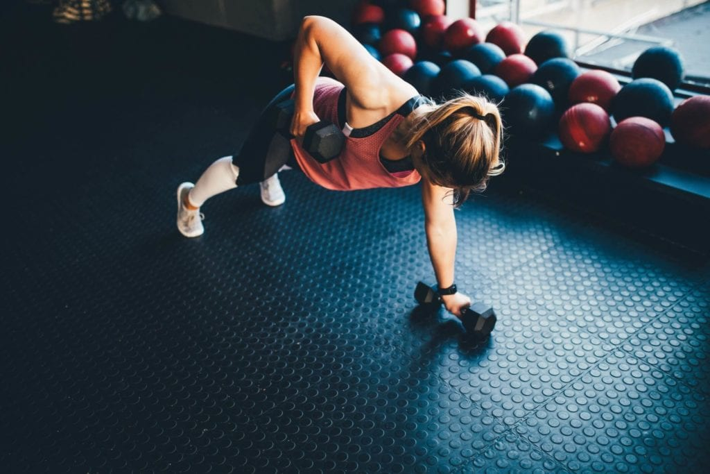 Woman in a gym doing renegade rows with dumbbells