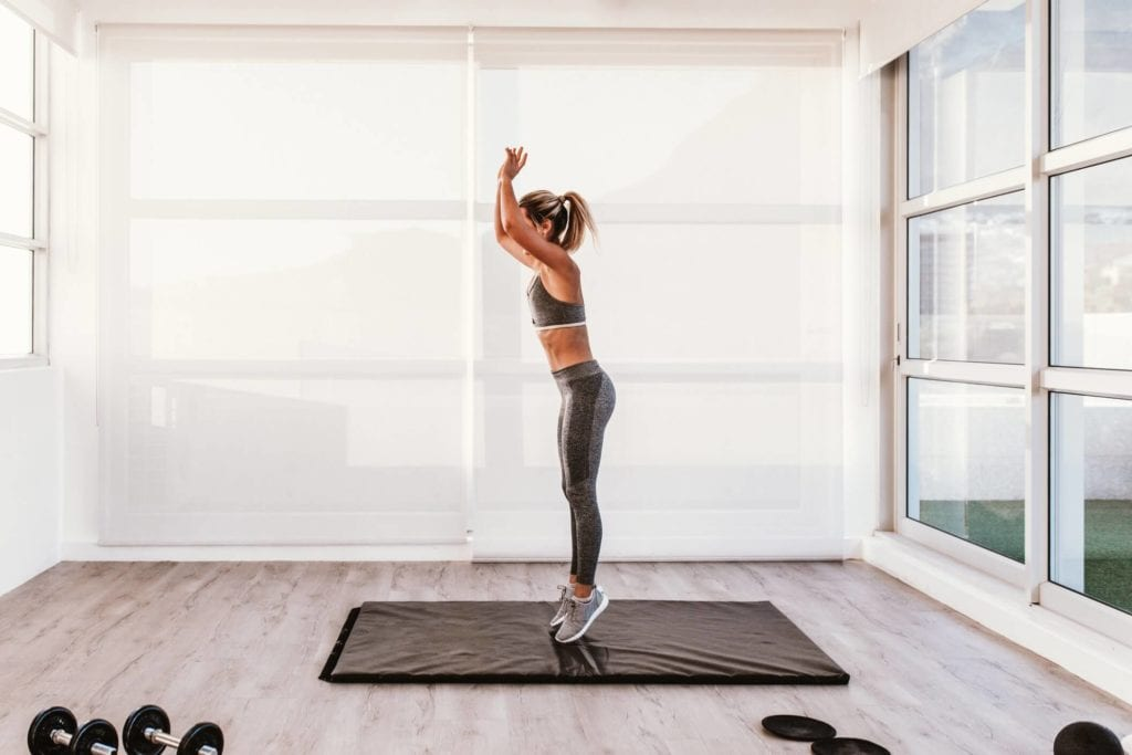 Woman in home studio space doing burpees